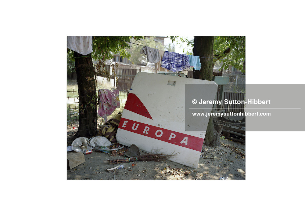 A piece of an airplane, bearing the insignia 'Europa',  stands against a tree in the village of Sintesti, in Romania, early August 2006. The Kalderari roma of Sintesti are by tradition metal workers, originally making alcohol stills, pots and pans, but now dealing in scrap metal such as this part of a plane. In January 2007 Romania will join the European Community. The roma of Sintesti have made large profits from their business enabling them to build large houses in the village of Sintesti, 20km from Bucharest, and to invest in fast, Western brand name cars such as BMW's, Mercedes and Porsche.