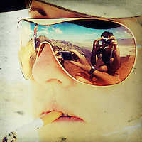 a young woman taking a picture is reflected in the sunglasses of another woman