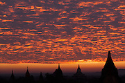 Six Stupas in silhouette with red sky and clouds at sunrise