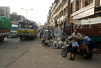 A father waits for the school bus with his children in a street in Pahar Ganj main bazar, New Delhi, India.