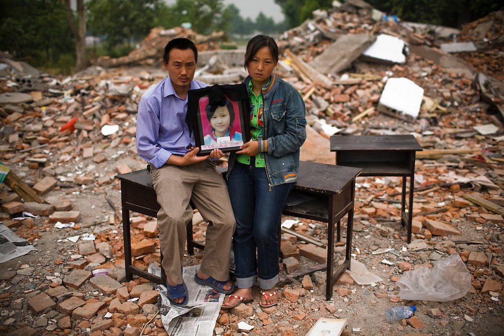 Zhang Fa Ming, 37, left, and Zhao Zheng Yin, 35, holding a picture of daughter Zhang Yi, 12,  are seen  at Fuxin No.2 Primary  School in Wufu, Sichuan province May 24, 2008.