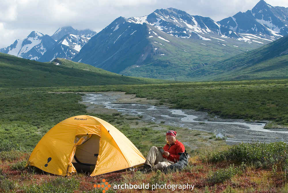 Woman reads a book beside her tent. Camping around Chuck Creek and Samuel Glacier in Canada's Yukon Territory.