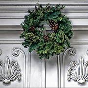 Arcgutectural details and Christmas Wreath with  pine cones decorations on front white door in Greenwich Village.
