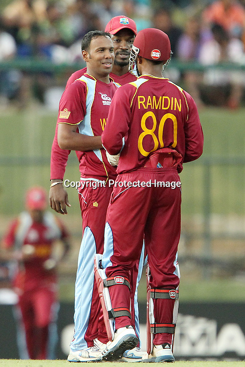 Samuel Badree of The West Indies celebrates the wicket of Brendon McCullum with Chris Gayle of The West Indies and Denesh Ramdin of The West Indies during the ICC World Twenty20 Super Eights match between The West Indies and New Zealand held at the  Pallekele Stadium in Kandy, Sri Lanka on the 1st October 2012<br /> <br /> Photo by Ron Gaunt/SPORTZPICS/PHOTOSPORT