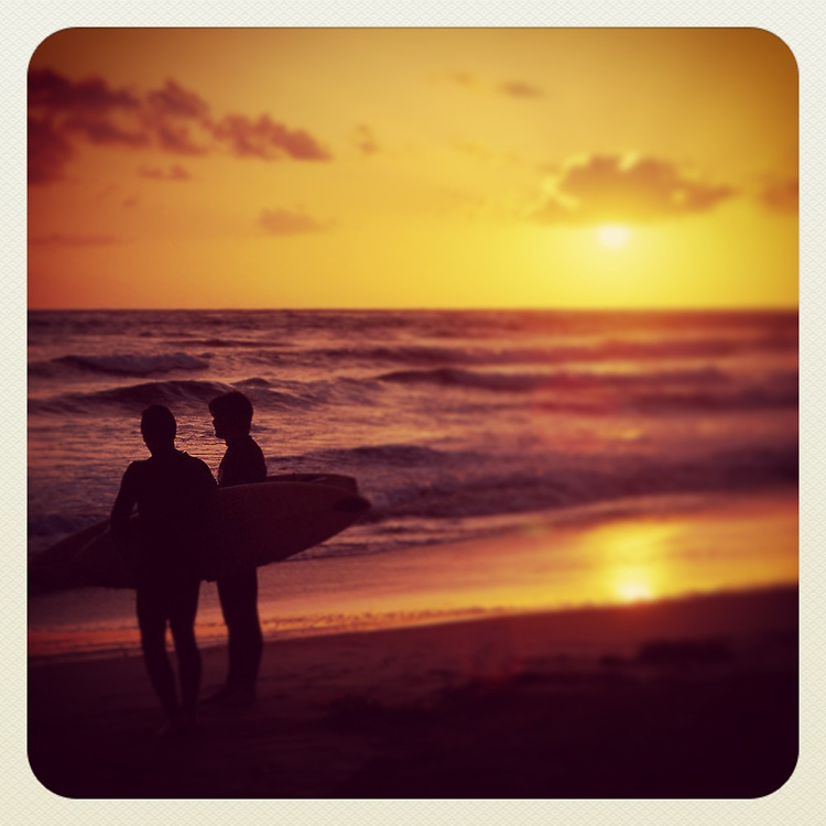 Silhouette Surfers with surf boards looking out to the Pacific Ocean at Sunset at Carlsbad State Beach, CA.