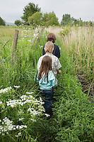 Three children (5-9) walking in countryside