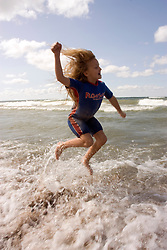 Young girl in wetsuit playing in water and jumping above the surf at the beach