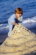 Boy building a sand castle at the beach.