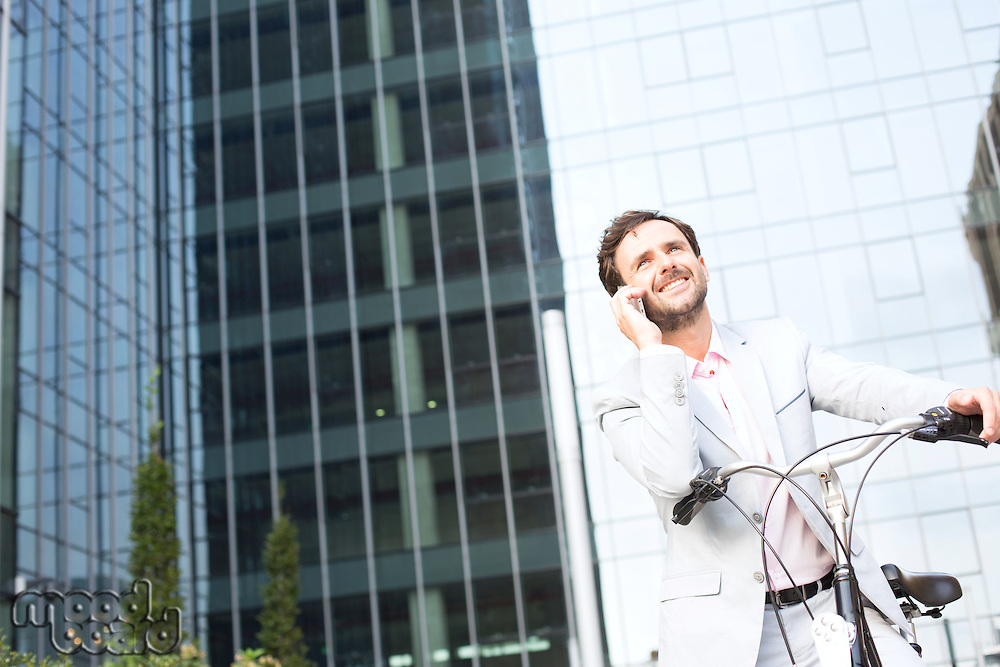 Low angle view of businessman answering mobile phone while sitting on bicycle outdoors