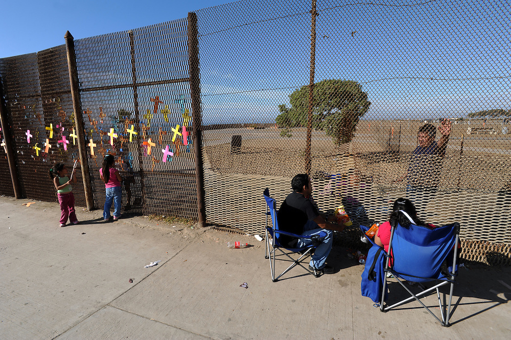 Tijuana Mexico ..the border in Playa Tijuana. Until recently divided families could meet at the fence to talk and even exchange small presents. Today the border is reinforced by a second fence on the US side which makes meetings like this one impossible...While working on this long term project 'La Frontera' I want to examine the cultural and humanitarian activities on both sides of a border that keeps the United States and Mexico apart with a wall of steel already 600 miles long. The turf wars of drug cartels, arms trafficking and rampant kidnappings turned cities like Tijuana into some of the most dangerous places on earth. Despite the violence many brave artists, photographers, architects, poets, humanitarians, teachers etc live and work in the shadow of the wall on both sides and have a positive influence on this region; they are the focus of my long term project along the border. (Over time I plan to cover the entire length from the Atlantic to the Pacific, these images were taken in and around Tijuana).© Stefan Falke