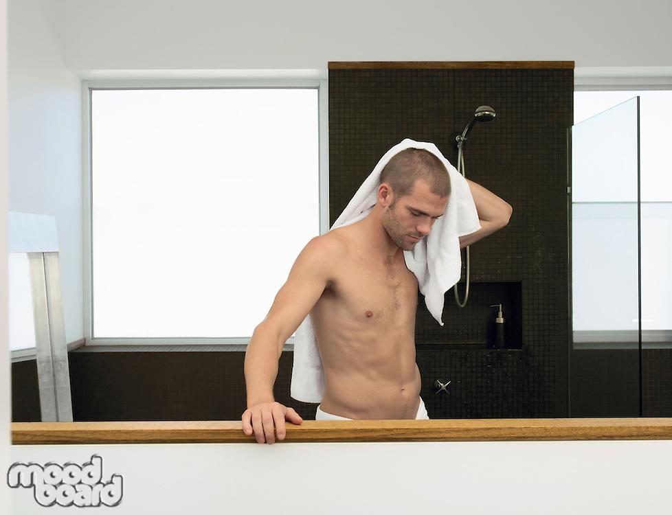 Man drying himself in bathroom