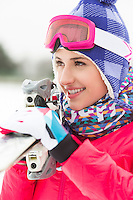 Beautiful young woman carrying skis outdoors