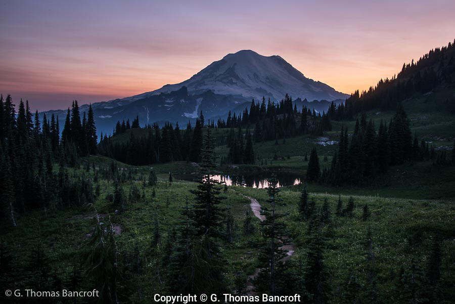 Sunset behind Mt Rainier from Naches Peak Loop Trail. The red in the sky is partly from the smoke from the many forest fires burning in Washington.