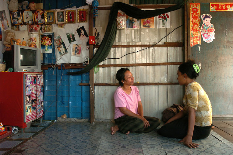Cambodia. Phnom Penh. 2006. Hen, an outreach worker with Chhouk Sar; a small NGO run by HIV positive former and current sex workers, talks to an x-sex worker, Sok San, in her home during a visit. Counseling and checking up on their clients is an important part of the home based care service. Sok San is receiving ARVs and OI medications through the Chouksar Program.