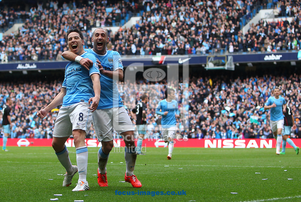 Samir Nasri of Manchester City and team-mate Pablo Zabaleta celebrate the opening goal against  West Ham United during the Barclays Premier League match at the Etihad Stadium, Manchester<br /> Picture by John Rainford/Focus Images Ltd +44 7506 538356<br /> 11/05/2014