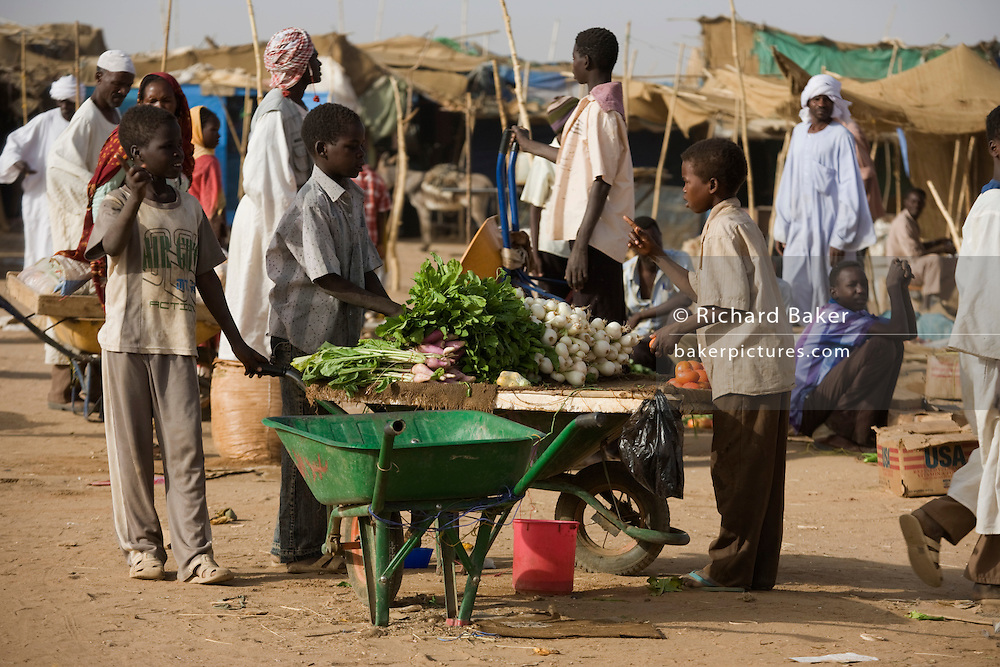 Daily souk market in the 4 sq km Abu Shouk refugee camp which is (disputedly) home to 38,000 displaced persons and families on the outskirts of the front-line town of Al Fasher (also spelled, Al-Fashir) in north Darfur.