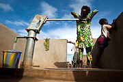 A girl fills a bucket with water from a hand pump in the village of Ambidedi Poste, Mali on Friday September 3, 2010.