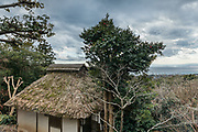 Oiso, Kanagawa prefecture, Japan, February 10 2017 - Keiji and Atsuko Suzuki's minka, traditional wooden house, is the last minka home in Oiso. The previous owner of the 3,000 sq. ft. house moved it from the shores of Lake Biwa, near Kyoto, 35 years ago.<br /> Detched house, the garden and the sea as seen from the main house.