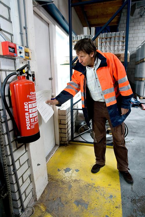 Nederland Dordrecht 24 september 2008 20080924 Foto: David Rozing ..Serie veiligheidsinspectie VROM. Blusinstallaties zijn verplicht in ruimten vol gevaarlijke stoffen, Vrom inspectie ( Sjef Strik in orange jack) controleert verfbedrijf / een brandblusser. ..Foto David Rozing