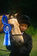 """Portrait of a young girl holding her First Prize winning pony at a gymkhana meeting, on 2nd July 1995, in Cheltenham, Gloucestershire, England. Gymkhana is an Indian Raj term which originally referred to a place where sporting events took place and referred to any of various meets at which contests were held to test the skill of the competitors. In the United Kingdom and east coast of the United States, the term gymkhana now almost always refers to an equestrian event for riders on horses, often with the emphasis on children's participation (such as those organised here by the Pony Club). Gymkhana classes include timed speed events such as barrel racing, keyhole, keg race (also known as """"down and back""""), flag race, and pole bending"""