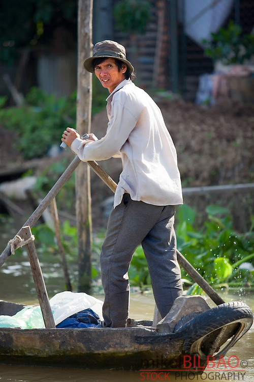 man rowing in a boat in a floating market. Can Tho City. <br /> Mekong delta, Vietnam, Asia