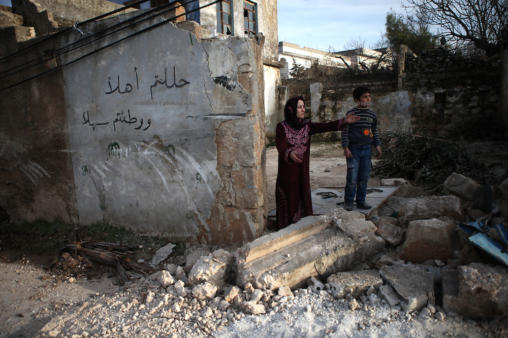 "A woman stand on her property destroyed by syrian troops. The arabic words written on the wall mean ""welcome"", which is common to write on the wall, when someone return from mekka. On 22. February the syrian army attacked the village of Kureen, Province of Idlib, Syria. Kureen was among the first villages in the northwest of Syria controlled by the opposition. Some villagers and members of the defence units escaped to surrounding olive orchards, when the attack begun in the early morning. A majority of the inhabitants didn´t manage to escape. The heavy shelling lasts 7 houres. Soldiers searched all houses, burnt some of them down, loote shops, stole cars and furniture. About 60 motorcycles were burnt down. Tanks demolished several houses. 6 men were executed. One woman died as a result of an heart attack."