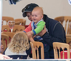Zara Phillips' baby Mia plays with her cousin Savannah Phillips' hair during lunch at Gatcombe this afternoon. Image ©Licensed to i-Images Picture Agency. 02/08/2014. Minchinhampton, United Kingdom. Gatcombe Festival of Eventing. Gatcombe Park. Picture by i-Images
