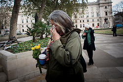 © Licensed to London News Pictures.06/12/2013. London, UK. A woman cries as she lays flowers at the statue of Nelson Mandela in Parliament Square, London to pay tribute to late former South African president Nelson Mandela following his death in Johannesburg.Photo credit : Peter Kollanyi/LNP
