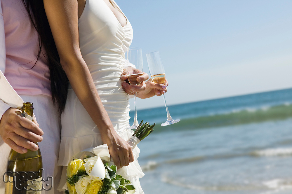 Bride and Groom with champagne at ocean (close-up)