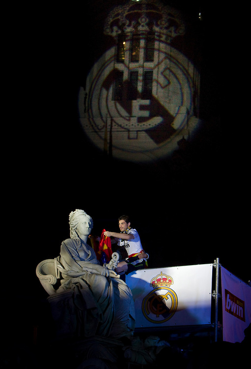 Real Madrid´s goalkeeper Iker Casillas drapes a flag around the neck of the Cibeles statue in Madrid in the early hours of Thursday, April 21, 2011after Real Madrid beat FC Barcelona wednesday to win the Copa del Rey.