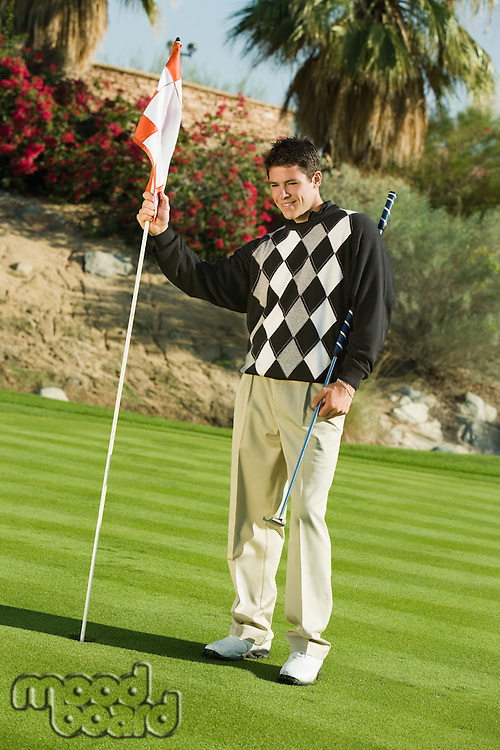 Golfer on Putting Green Holding Pin