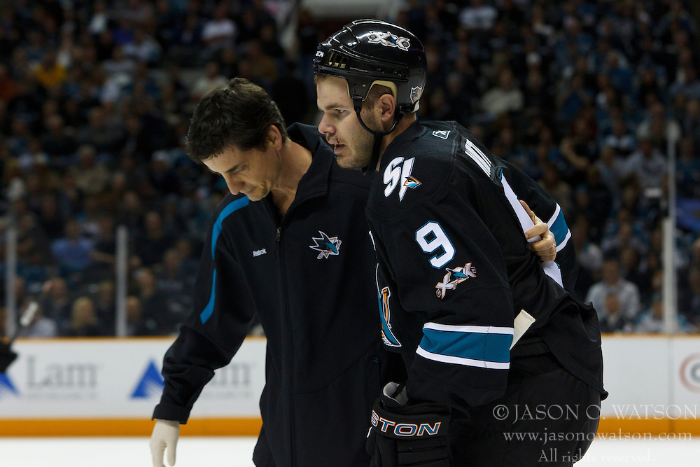 April 14, 2011; San Jose, CA, USA;  San Jose Sharks defenseman Ian White (9) is assisted to the bench by trainer Ray Tufts (left) after being knocked into the boards by Los Angeles Kings center Jarret Stoll (not pictured) during the first period at HP Pavilion. San Jose defeated Los Angeles 3-2 in overtime. Mandatory Credit: Jason O. Watson / US PRESSWIRE