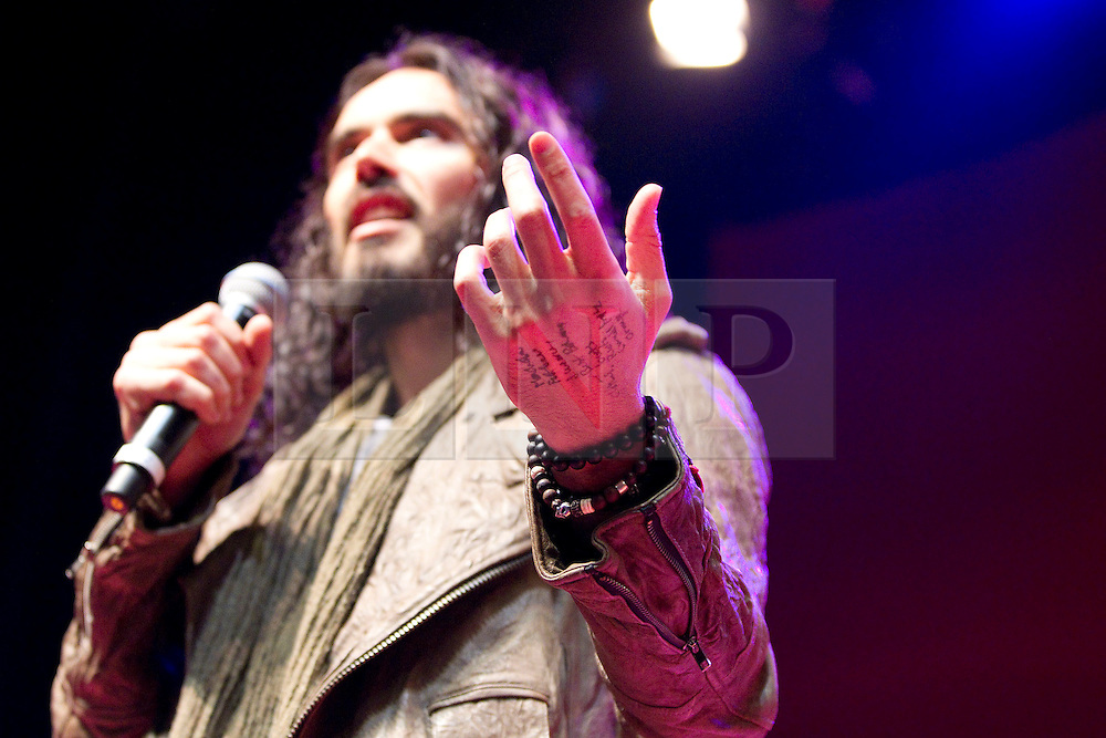 © Licensed to London News Pictures. 16/06/2012. Manchester , UK . Notes written on Russell Brand's hand . Russell Brand introduces The Dalai Lama at the Manchester Arena , Greater Manchester , at the Stand Up and Be the Change youth event . The Dalai Lama is on a 10 day tour of the UK . Photo credit : Joel Goodman/LNP