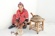 Moroccan woman cracking argan nuts to press them for oil.
