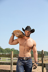 shirtless cowboy with wood over his shoulder