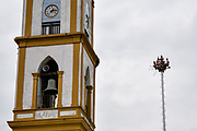 Voladores prepare to performs in front of the Church of the Assumption in Papantla, Veracruz, Mexico. The Danza de los Voladores is a indigenous Totonac ceremony involving five participants who climb a thirty-meter pole. Four of these tie ropes around their waists and wind the other end around the top of the pole in order to descend to the ground. The fifth participant stays at the top of the pole, playing a flute and a small drum. The ceremony has been inscribed as a Masterpiece of the Oral and Intangible Heritage of Humanity by UNESCO.