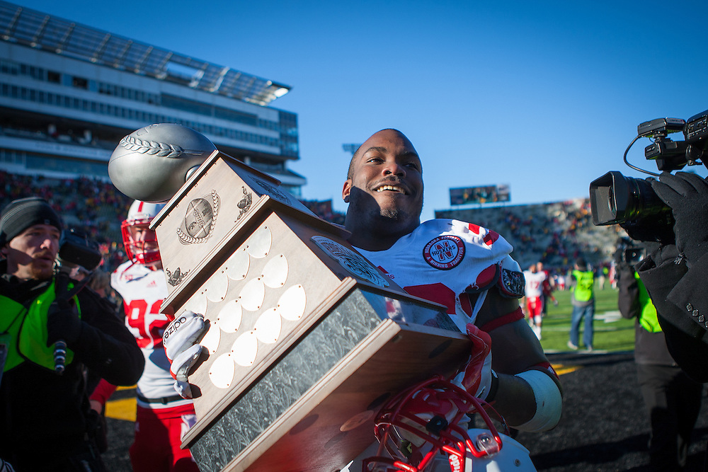 Eric Martin #46 of the Nebraska Cornhuskers hoists the Heroes Game Trophy after Nebraska's 13-7 win on Nov. 23, 2012 at Kinnick Stadium.