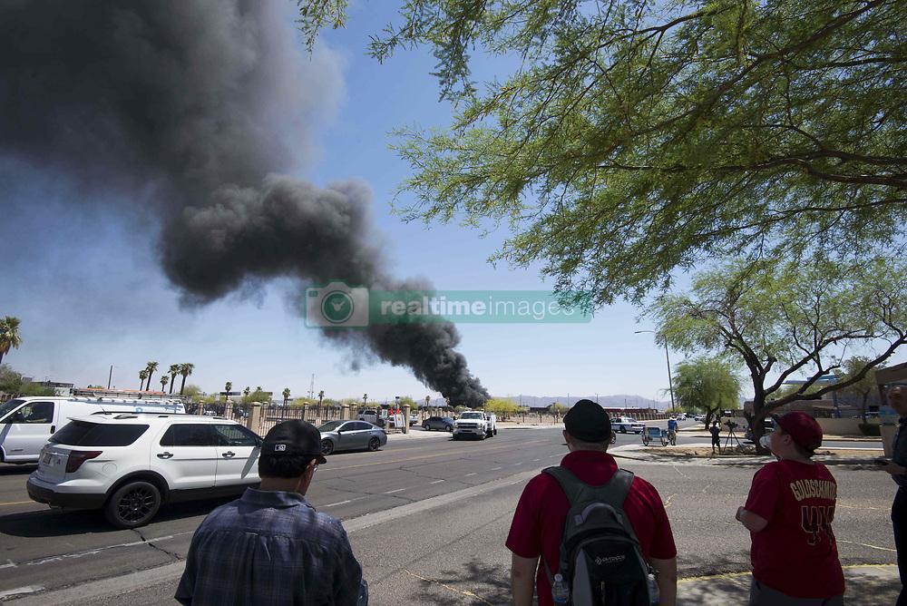 April 27, 2018 - Phoenix, Arizona, U.S - Pedestrians watch as firefighters work the scene of a fire at a recycling plant near 13th Avenue and Harrison Street in Phoenix, Arizona, on Friday, April 27, 2018. (Credit Image: © Ben Moffat/via ZUMA Wire via ZUMA Wire)