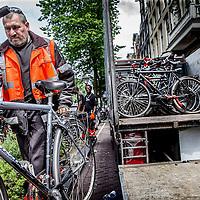 Nederland, Amsterdam, 24 juni 2016.<br />Elke maand organiseerde het Fietsdepot voor professionele opkopers een veiling van de fietsen die niet binnen zes weken zijn opgehaald door hun eigenaar. Maandagochtend vindt voor de laatste keer een fietsveiling plaats. Voor die speciale gelegenheid neemt wethouder Pieter Litjens (Verkeer) de veilinghamer ter hand.<br />Vanaf 1 juli is het Haarlemse bedrijf TradeFRM verantwoordelijk voor de verkoop van niet-opgehaalde fietsen aan handelaren en aan sociale&nbsp;werkprojecten. &quot;Ook het niet verkoopbare materiaal zal door TradeFRM op de meest duurzame manier worden gerecycled en hergebruikt,&quot; aldus de gemeente.<br />Alle door de gemeente weggeknipte fietsen komen terecht op het terrein van het Fietsdepot in het Westelijk Havengebied. Amsterdammers kunnen daar terecht om hun weggeknipte fiets weer op te halen. Dat kost sinds 1 januari dit jaar 22,50 euro. Daarvoor was dat 15 euro. Thuis laten bezorgen kan ook, voor 50 euro. Iets minder dan de helft van de fietsen worden door de eigenaar opgehaald.<br />Op de foto: Fietsen die te lang langs de grachten blijven staan worden door de Gemeente weggesleept.<br /><br /><br />Foto: Jean-Pierre Jans