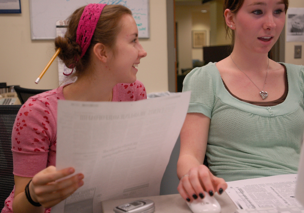 Copy editors Sarah McCoy, right, and Angie Weaver review a print-out of a page from the next day's paper and make changes on the computer during their Feb. 22 late night at The Post.