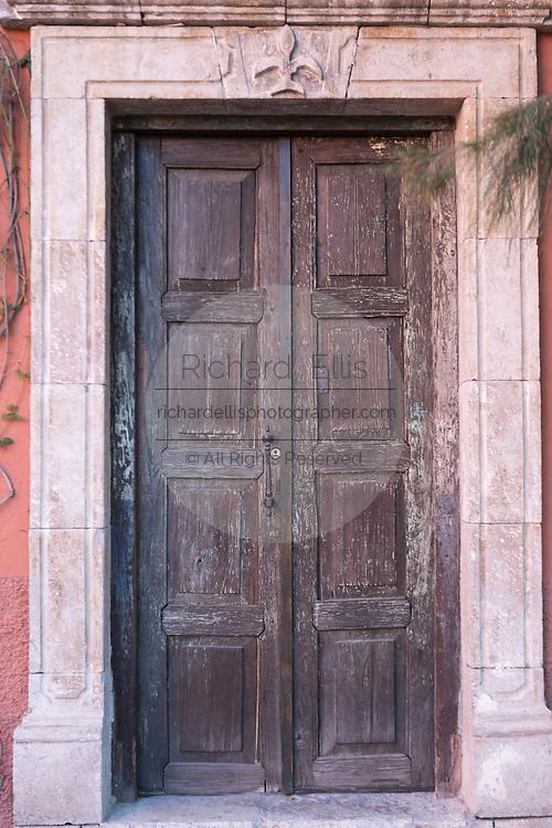 A colonial style wooden door at the plaza de San Felipe Neri in San Miguel de Allende, Mexico.