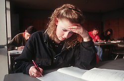 Secondary school girl sitting at desk in classroom answering exam paper,