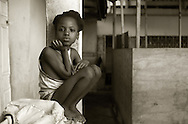 A little girl looks toward the photographer while sitting at an orphanage in Port-Au-Prince Haiti, January 27, 2012.