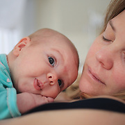 A two month old baby girl rests in bed with her mother while observing her environment. Photo Tim Clayton