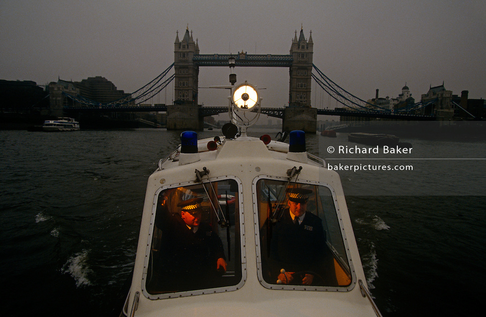 Two Metropolitan Police officers patrol the tidal waters River Thames near Tower Bridge in London, England. In their small boat used to police and often make searches of the river in central London, their searchlight watches for people in the water - especially on Fridays and around New year. The Underwater and Confined Space Search Team (UCSST), are part of the Marine Support Unit and based at Wapping. They also carry out searches in canals, ponds, lakes and reservoirs. It was set up as a full time unit in 1964. One of their most distressing jobs, however, is recovering bodies from the River. On average over 50 people lose their lives in the Thames each year and about 80% of these are by suicide (usually by jumping off one of the many bridges that cross the Thames).