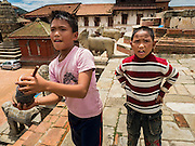 02 AUGUST 2015 - BHAKTAPUR, NEPAL:  Boys fly their kite from the top of a temple destroyed by the Nepal earthquake. The Nepal Earthquake on April 25, 2015, (also known as the Gorkha earthquake) killed more than 9,000 people and injured more than 23,000. It had a magnitude of 7.8. The epicenter was east of the district of Lamjung, and its hypocenter was at a depth of approximately 15 km (9.3 mi). It was the worst natural disaster to strike Nepal since the 1934 Nepal–Bihar earthquake. The earthquake triggered an avalanche on Mount Everest, killing at least 19. The earthquake also set off an avalanche in the Langtang valley, where 250 people were reported missing. Hundreds of thousands of people were made homeless with entire villages flattened across many districts of the country. Centuries-old buildings were destroyed at UNESCO World Heritage sites in the Kathmandu Valley, including some at the Kathmandu Durbar Square, the Patan Durbar Squar, the Bhaktapur Durbar Square, the Changu Narayan Temple and the Swayambhunath Stupa. Geophysicists and other experts had warned for decades that Nepal was vulnerable to a deadly earthquake, particularly because of its geology, urbanization, and architecture.      PHOTO BY JACK KURTZ