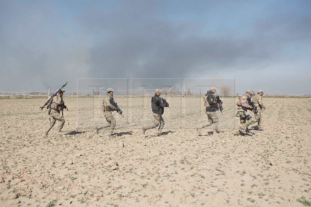 © London News Pictures. 24/02/2017. Mosul, Iraq. Iraqi Emergency Response Division soldiers run across across a recently liberated field around 1.5km south of western Mosul. Operations to retake western Mosul from the Islamic State continued today and saw Iraqi troops enter the edges of southern neighbourhoods. Matt Cetti-Roberts/LNP