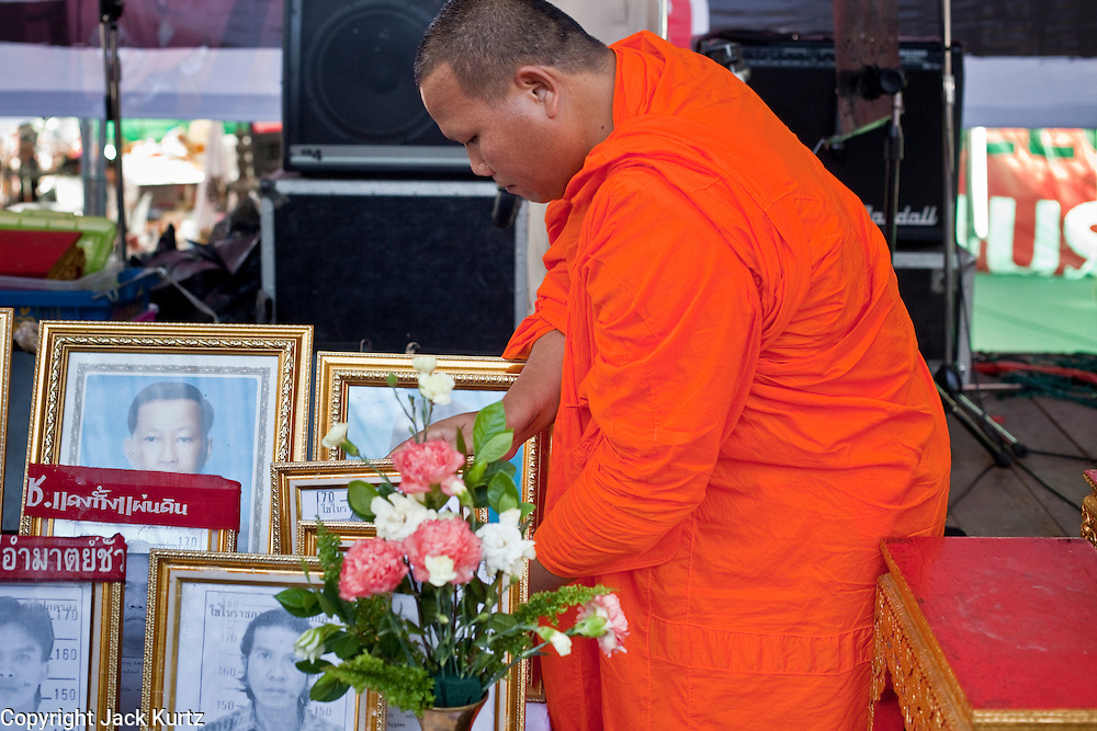"10 MAY 2010 - BANGKOK, THAILAND: A Buddhist monk sets up photos of Red Shirts killed in street violence on April 10 before a memorial service Monday. The Red Shirts held a special memorial service at their main protest site in Ratchaprasong Intersection Monday with Buddhist monks leading chants to mark the one month anniversary of the street violence on April 10 that left 25 dead and more than 800 injured. Thai media is reporting that Prime Minister Abhisit Vejjajiva has given the Red Shirts has given the Red Shirts until the end of today to either accept his ""Road Map for Reconciliation"" and end the protest or face unspecified consequences widely thought to include a military crackdown.   Photo by Jack Kurtz / ZUMA Press"