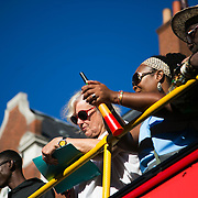 Judges up high in a double decker, marking the various floats and groups dancing by. busHackney carnival 2016 took place on a hot Indian summer's day, September 2016 with the streets full of partying people.