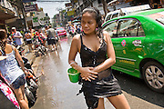 "Apr. 13, 2010 - Bangkok, Thailand: A Thai woman stands in the street after getting doused with water during Songkran festivities on a soi off of Sukhumvit Rd in Bangkok Tuesday. Songkran is the Thai New Year's holiday, celebrated from April 13 - 15. This year's official celebrations have been cancelled because of the Red Shirt protests but Thais are still marking the holiday. It's one of the most popular holidays in Thailand. Songkran originally was celebrated only in the north of Thailand, and was adapted from the Indian Holi festival. Except the Thais throw water instead of colored powder. The throwing of water originated as a way to pay respect to people, by capturing the water after it had been poured over the Buddhas for cleansing and then using this ""blessed"" water to give good fortune to elders and family by gently pouring it on the shoulder. Among young people the holiday evolved to include dousing strangers with water to relieve the heat, since April is the hottest month in Thailand (temperatures can rise to over 100°F or 40°C on some days). This has further evolved into water fights and splashing water over people riding in vehicles. The water is meant as a symbol of washing all of the bad away and is sometimes filled with fragrant herbs when celebrated in the traditional manner. Photo by Jack Kurtz"